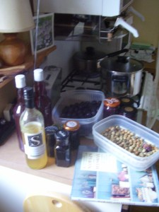 Elderberries stweing in background, plums waiting their turn in middle, some plum gin and edlerflower cordial on the left, finished jars elderberry syrups middle and hazelnuts to the right